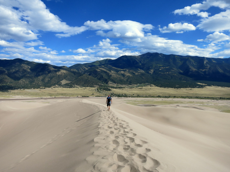 A sandy hike with the rugged Sangre De Cristos in the background