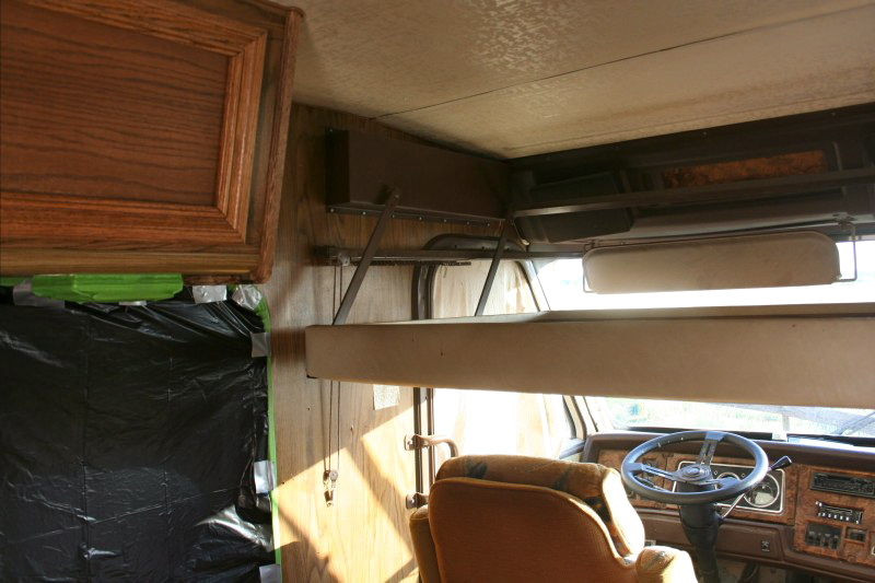 wood paneling behind the over can bed in a motorhome