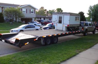 Vintage camper trailer on a flat bed trailer