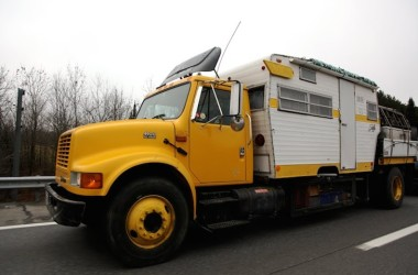 Yellow Shasta trailer on a flatbed truck