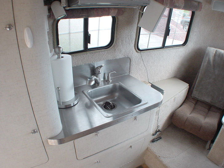 Stainless steel sink in the kitchen of this Scamp fifth wheel trailer