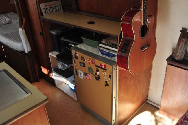 Refrigerator and guitar hanging in an Airstream