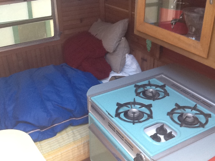 Stove and sleeping area inside small RV