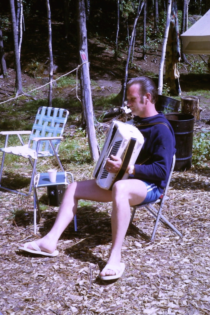Playing accordion at campsite