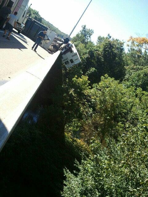 Truck camper dangles from overpass
