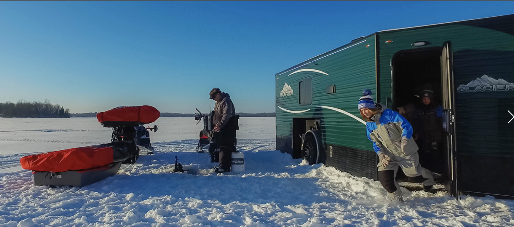 An Ice Fishing RV sits close to the ice and has roof for the whole family.