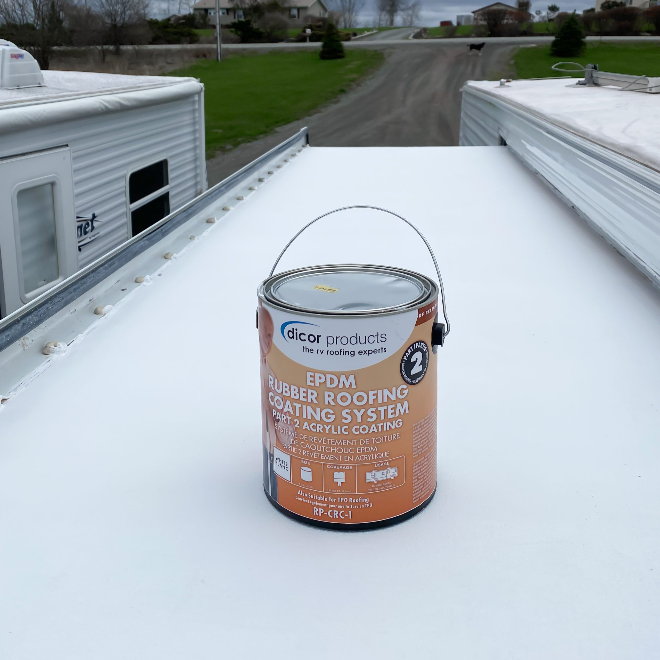 Can of RV rubber roof coating product on an RV slide out.