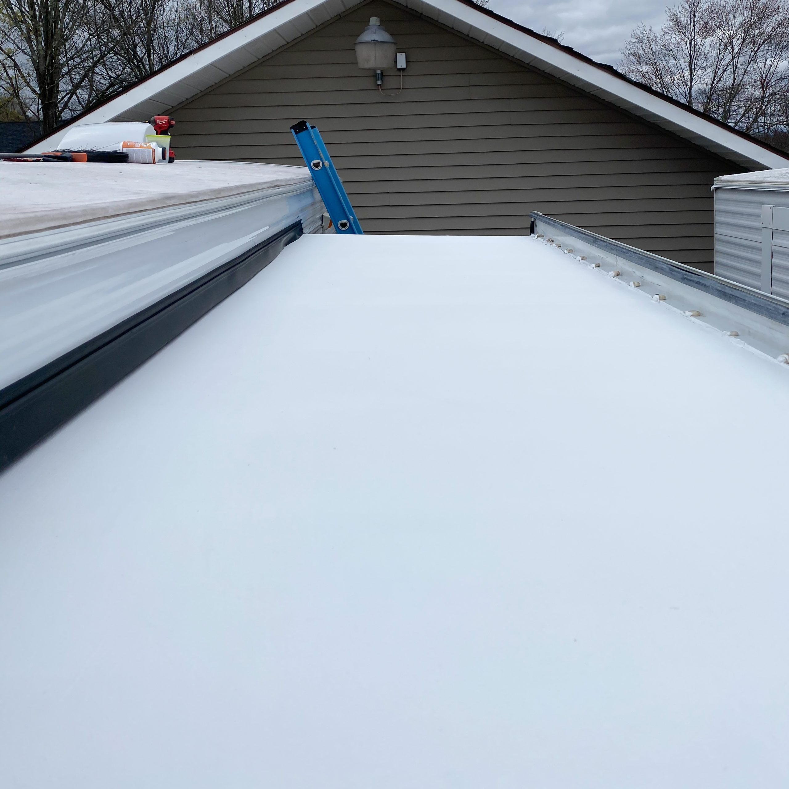 Fresh RV rubber roof coating on an RV slide out.