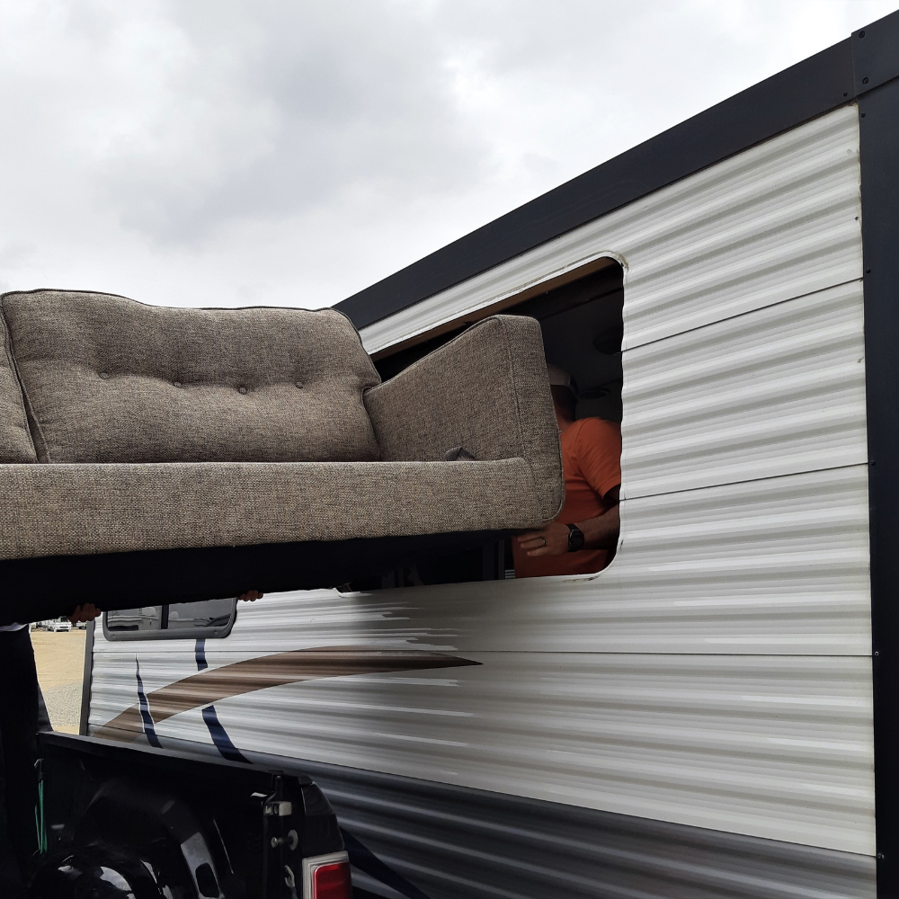 Couch being moved through a removed RV window opening - RV window replacement