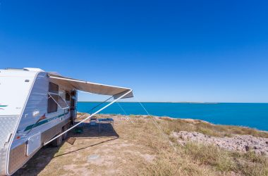 RV awning extended on travel trailer in front of water view