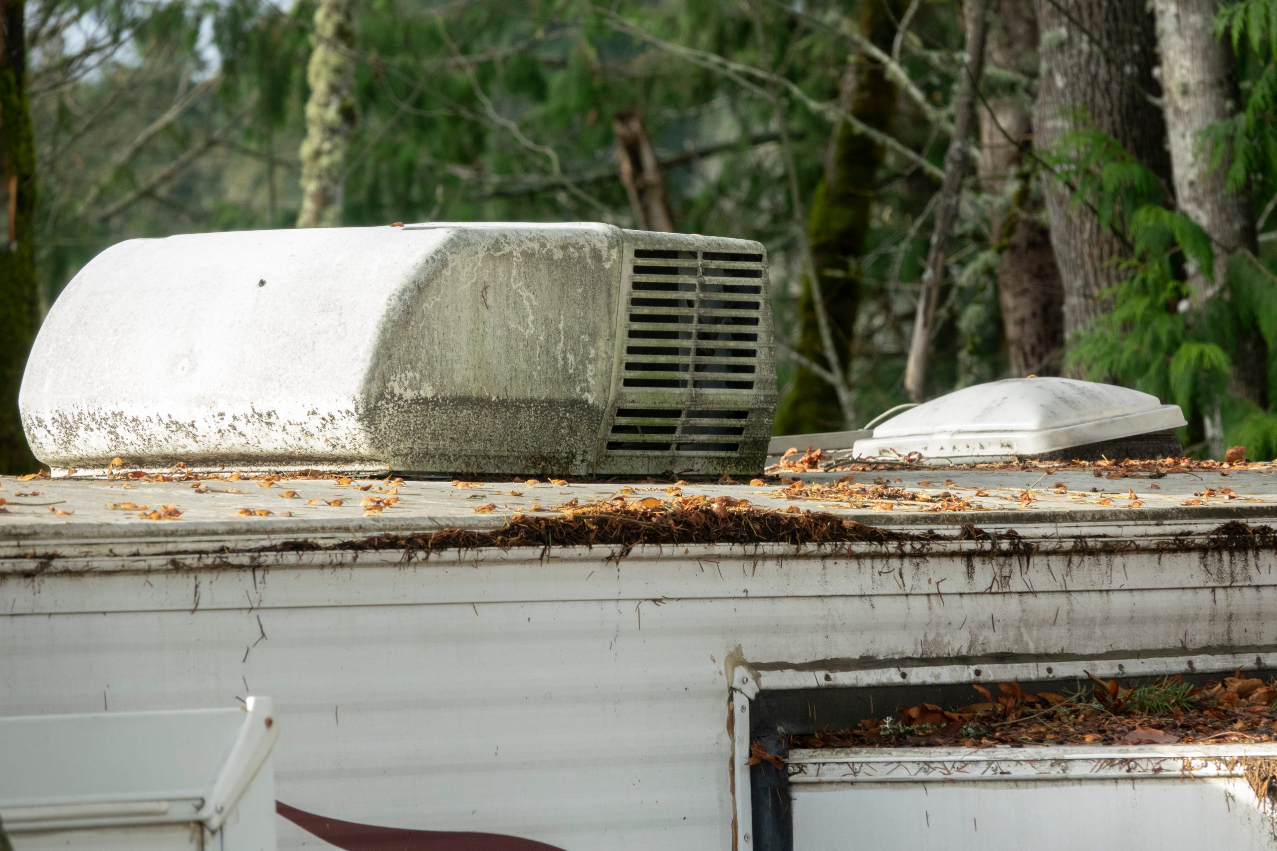Very dirty RV roof and A/C unit