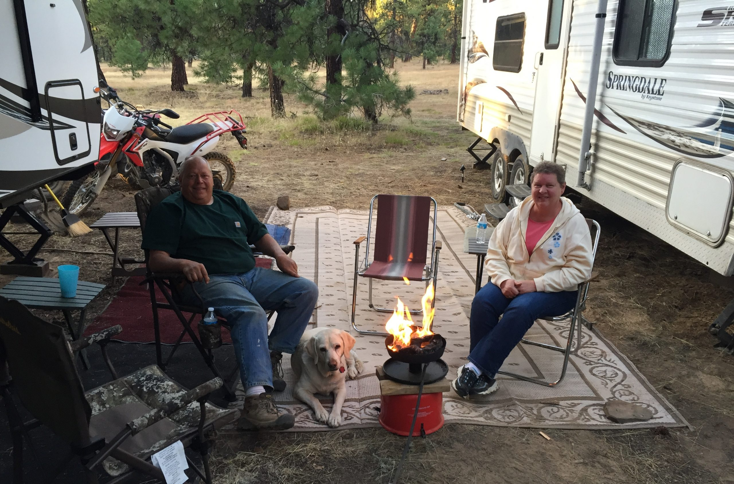 People sitting next to portable fire pit