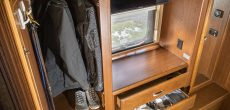 Clothes hung up and in drawers of an RV closet