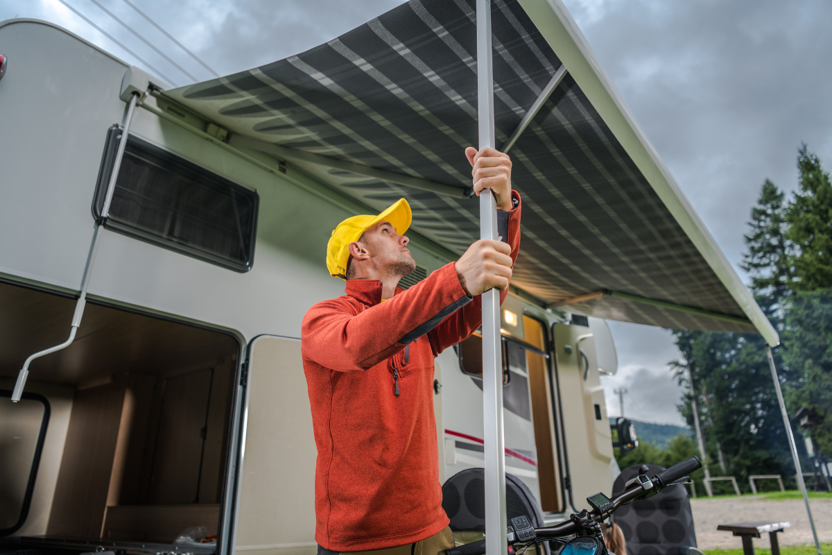 Man instaling awning support leg under RV awning - electric RV awning
