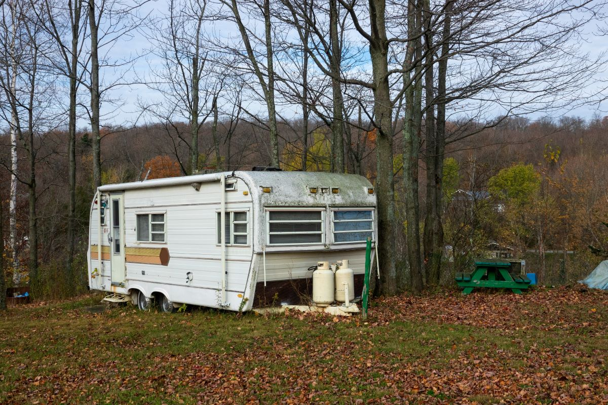 Old, rundown RV parked under some trees in need of a DIY RV rubber roof replacement