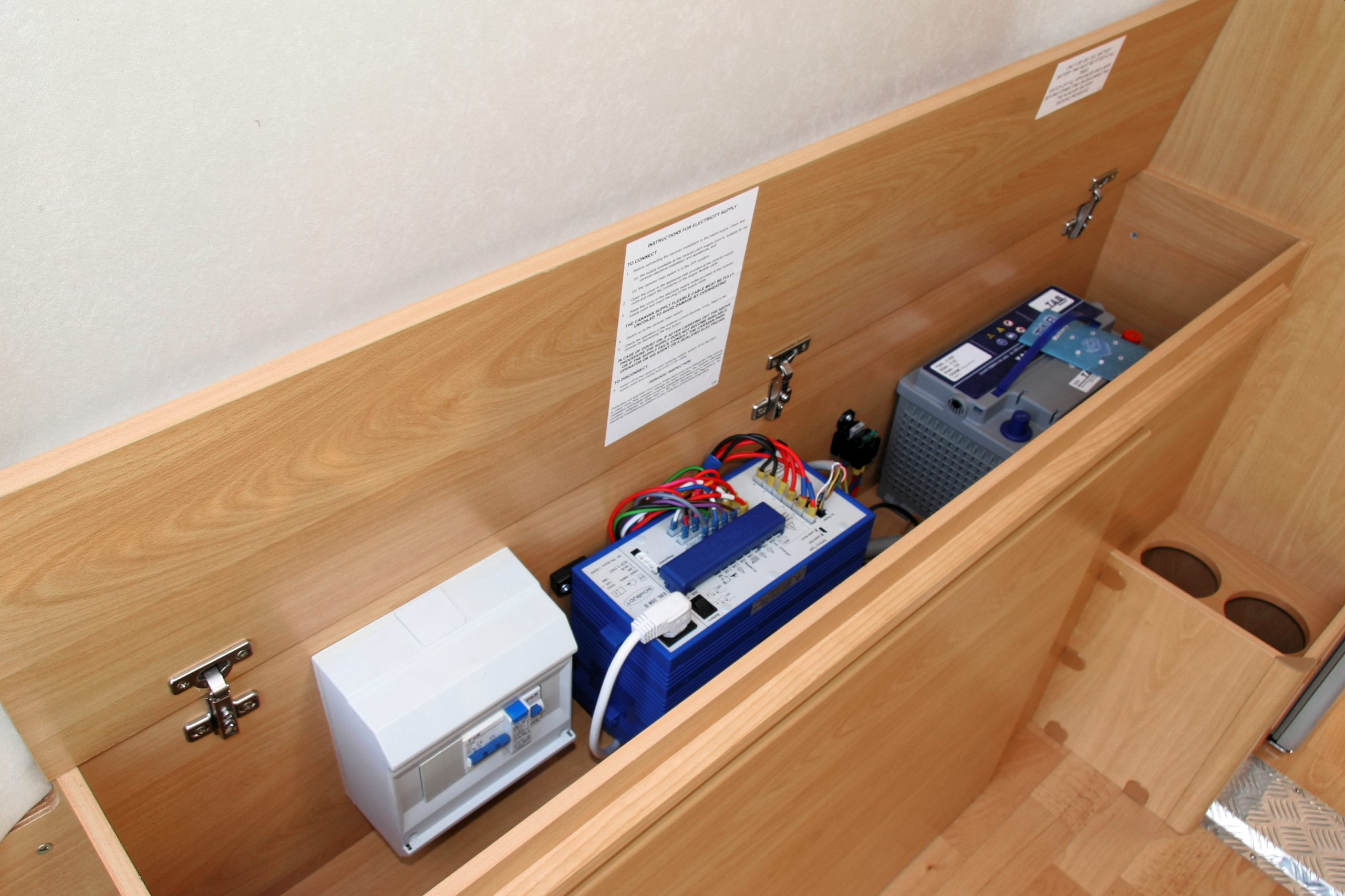 RV battery and electrical components inside storage cabinet - RV power converter troubleshooting