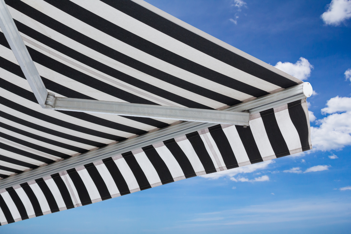 black and white striped awning extended on a bright day - electric RV awning