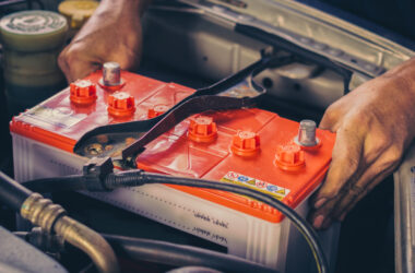 Hands place RV battery in vehicle