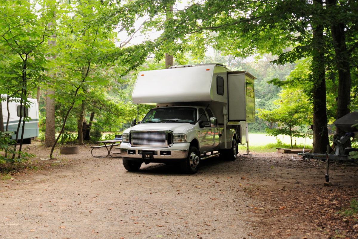 Truck with camper in bed set up on lake side campsite - camper jacks