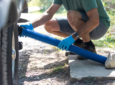 Man setting up RV sewer hose with a rock as a weight - RV accessories
