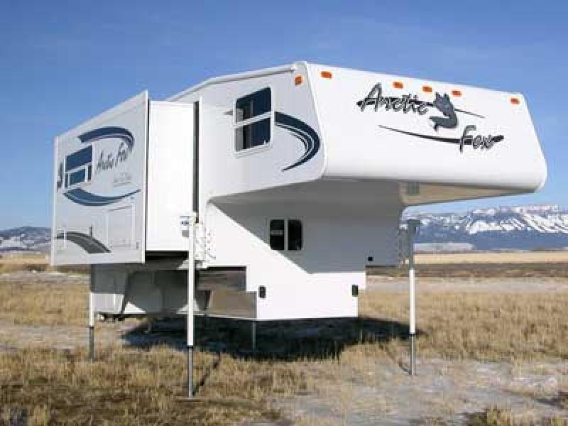 Truck camper set up on camper jacks in a mountain setting - camper jacks