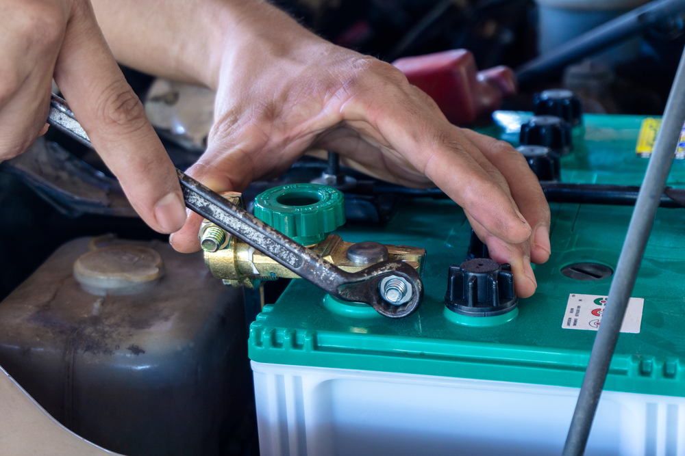 Mechanic attaches lead to an RV battery.