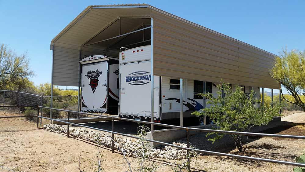 Two RVs parked under a carport in a rural setting - DIY RV carport