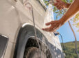 Person washing their hands with an outdoor RV shower - RV water heater leaking
