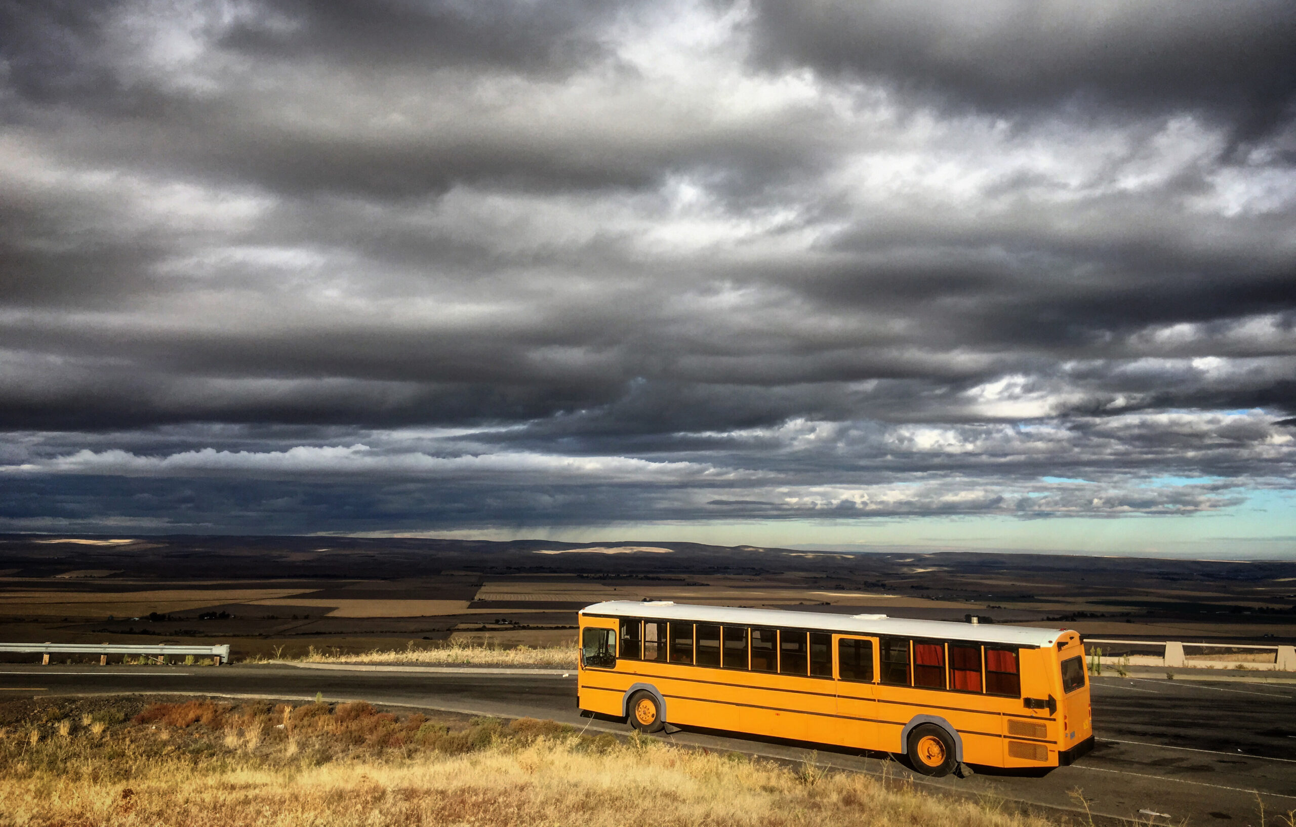 School Bus Camper in front of stormy clouds