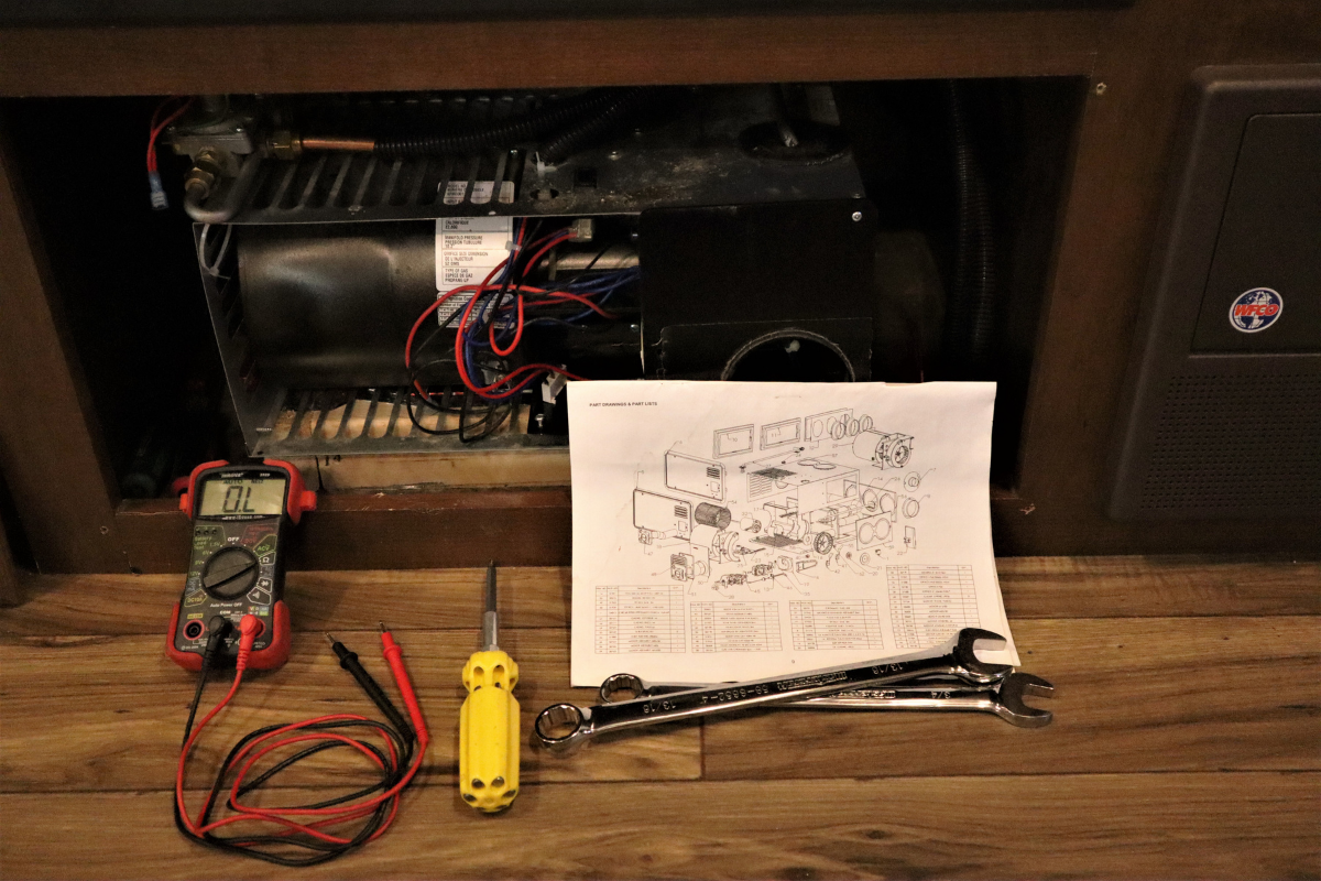 Multimeter and tools layed ouit beside RV furnace - RV furnace blowing cold air